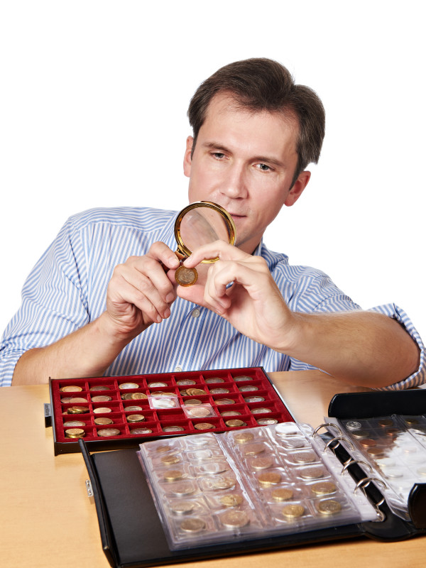 Man numismatist examines  coin with magnifying glass